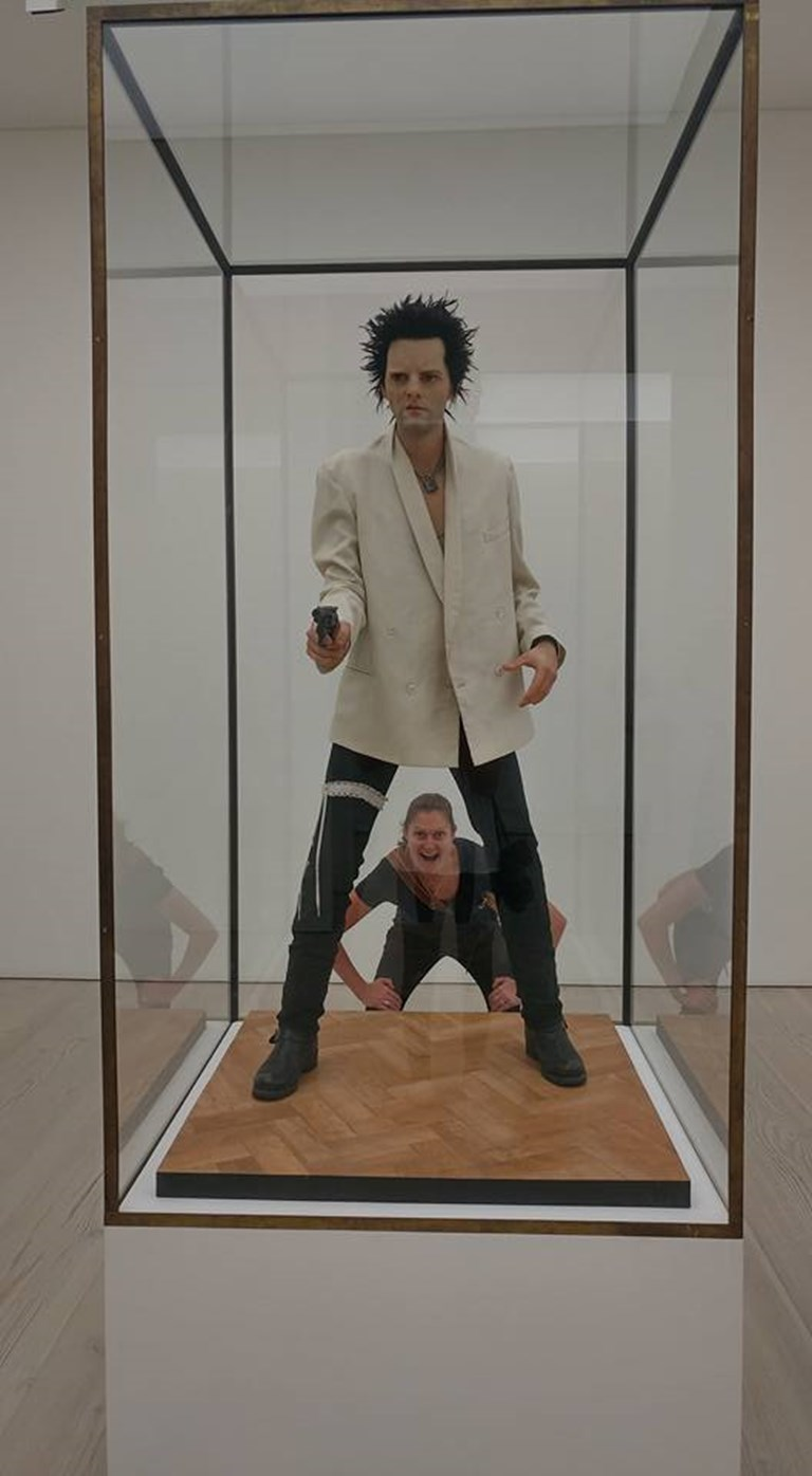 life size statue of man in white tuxedo, with a gun and a suspender belt.